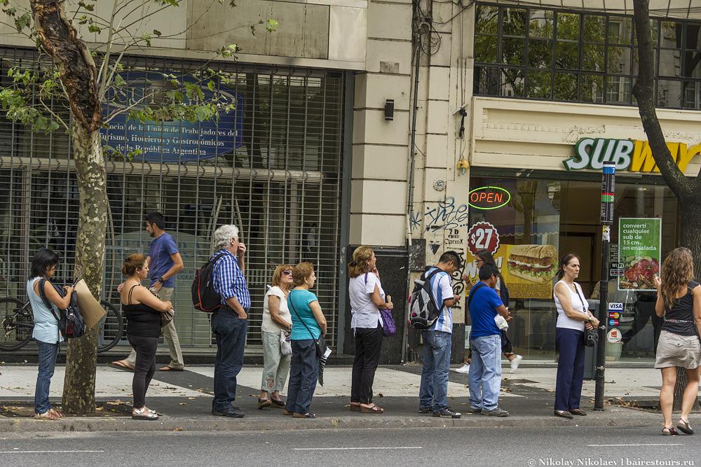 42. Удивительная организованность, люди ждут автобус и выстраиваются в очередь.